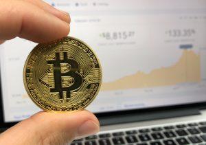 dos dedos sujetando una moneda en primer plano y una pantalla de fondo